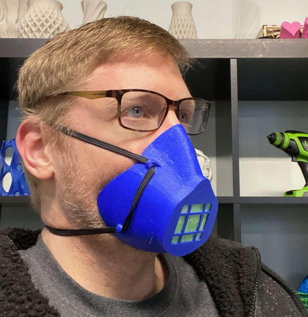 Man with glasses wears blue 3D printed mask