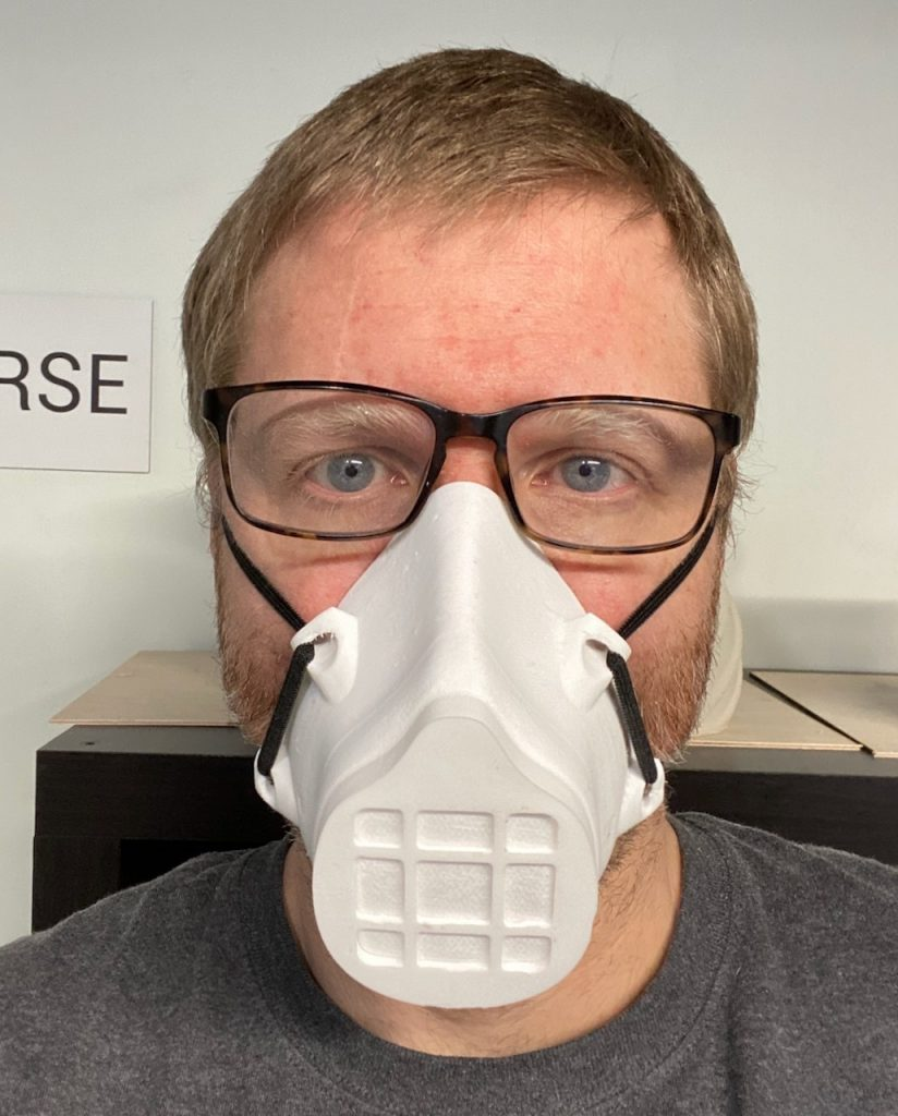 Man with glasses wears white 3D printed mask