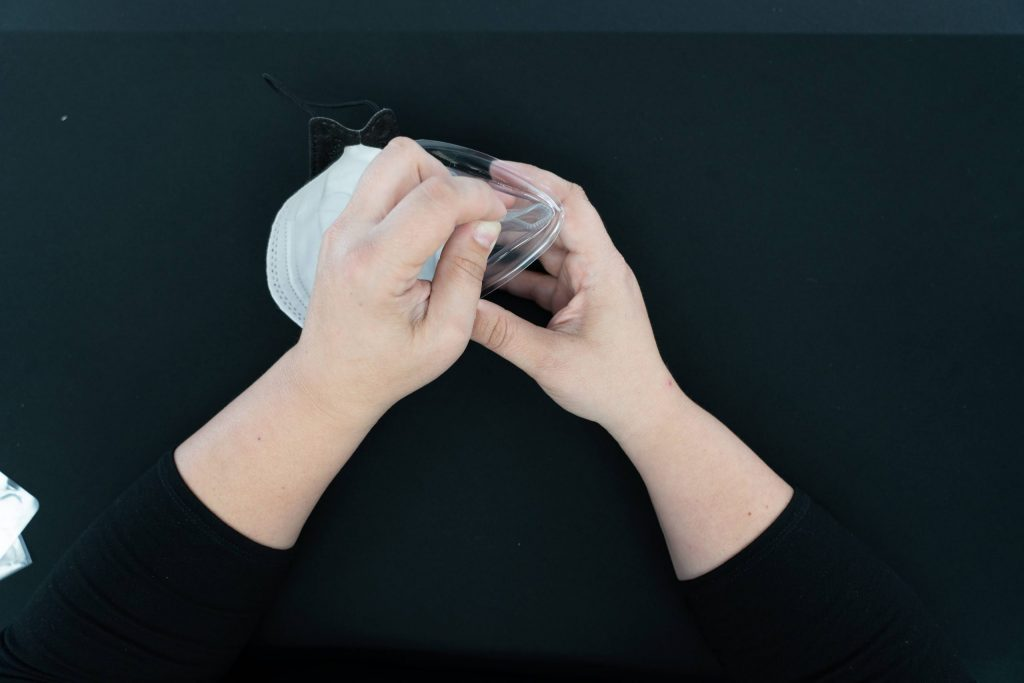 """Use included clear comfort strips to create an airtight cradle for the bridge of your nose. Remove the strip from it's plastic backing. Fold in half, sticky side out and insert the fold into the """"V"""" at the bridge of the nose. Unfurl the clear comfort strip to make a soft airtight """"cradle"""" for your nose."""