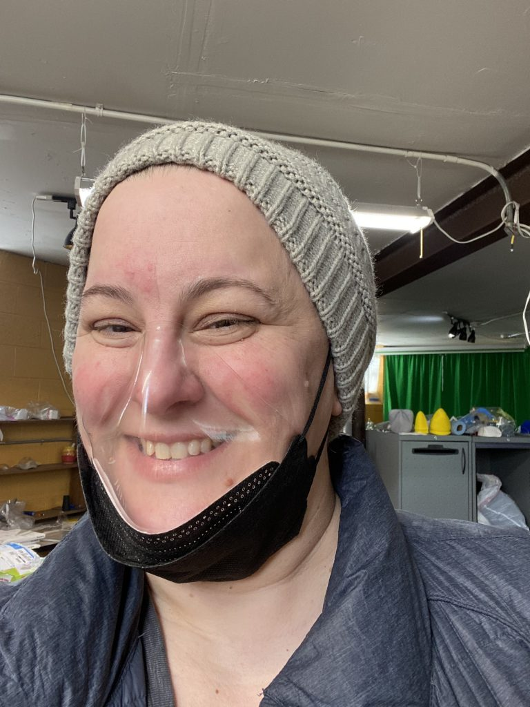Woman wears a prototype of mask design with smile clearly visable