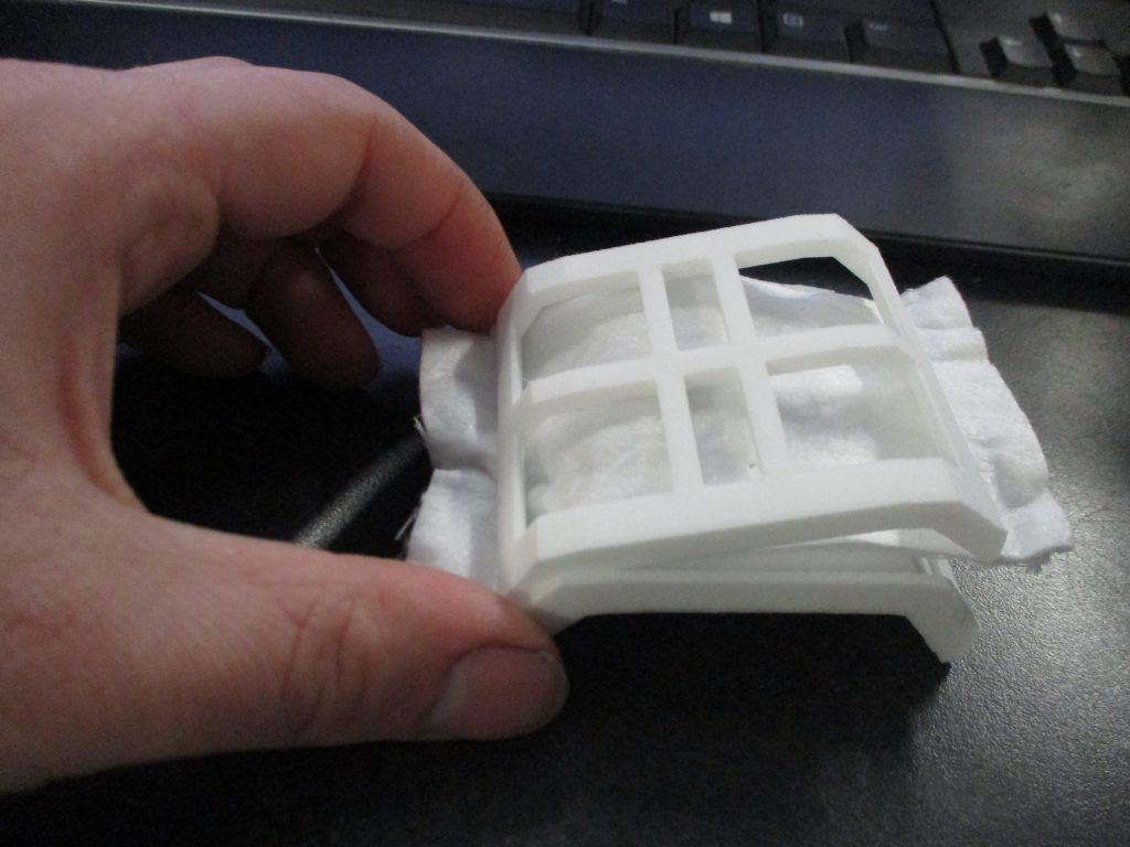 """5. Work the filter piece in between the """"moats"""" at the edges of the filter area as you are inserting the first corner of the insert."""