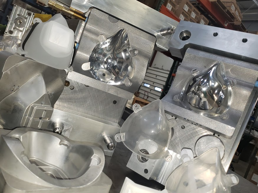 Injection molding equipment for making masks. Mold is open with masks on top.on the table.