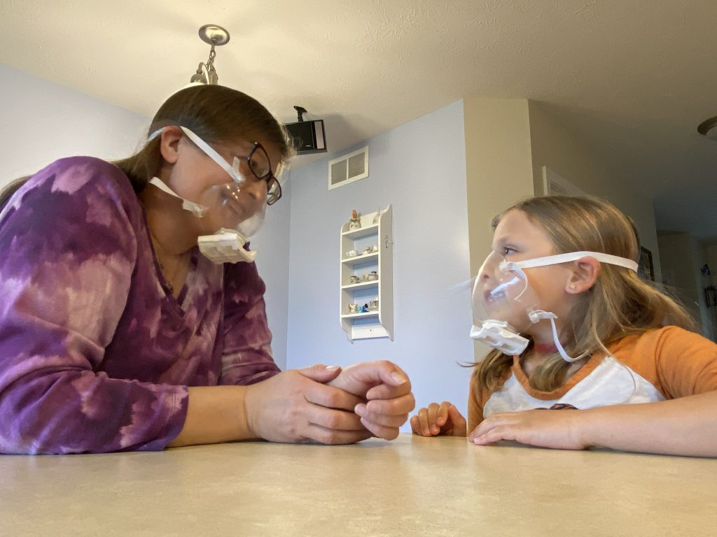 Woman and child both wear clear masks and face each other over a kitchen table