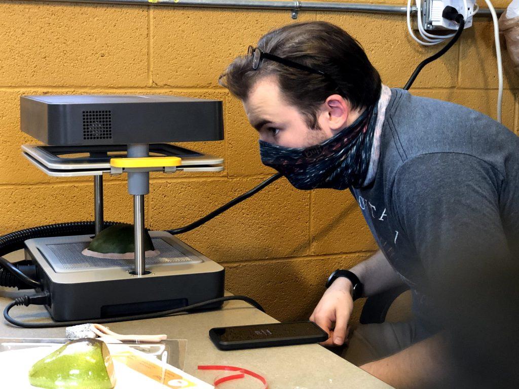 Man wearing a bandana looks into vacuum forming machine